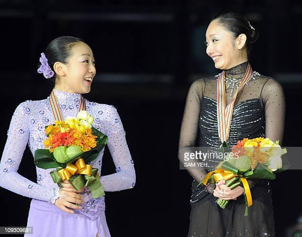 Mao Asada of Japan and compatriot Miki Ando talk while on the podium after finishing second and first respectively in the ladies free skating event...