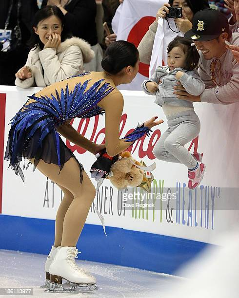 Mao Asada of Japan gets a gift from a young fan during the ladies free dance of day three at Skate America at Joe Louis Arena on October 20 2013 in...
