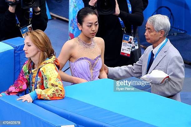Mao Asada of Japan is consoled by her coach Nobuo Sato after competing in the Figure Skating Ladies' Short Program on day 12 of the Sochi 2014 Winter...