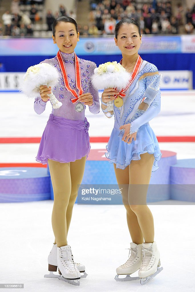 Mao Asada of Japan with silver medal and Akiko Suzuki of Japan with a gold medal pose for photograghs in the women's singles during day two of the ISU Grand Prix of Figure Skating NHK Trophy at Makomanai Sekisui Heim Arena on November 12, 2011 in Sapporo, Japan.