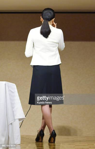 Mao Asada threetime world figure skating champion and silver medalist at the 2010 Vancouver Olympics wipes away tears with her back to reporters at...