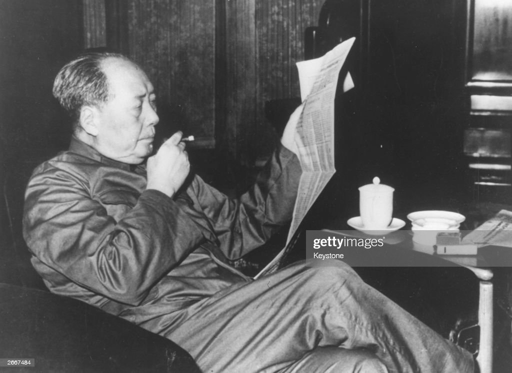 Mao Tse-tung (1893-1976), Chinese Communist leader who was chairman of the Communist party of China and the principal founder of the People's Republic of China, reading a newspaper and smoking a cigar.