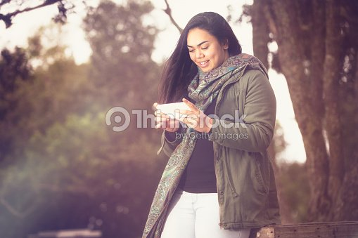 Maori girl using her smartphone. : Stock Photo