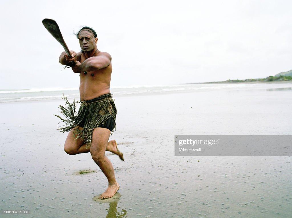 Maori man performing Haka Powhiri on beach : Stock Photo