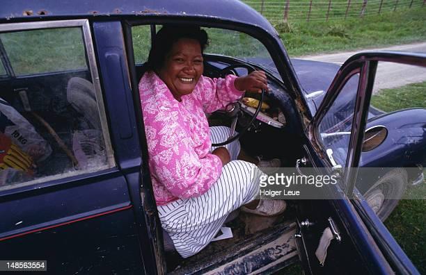 Maori woman in old car.