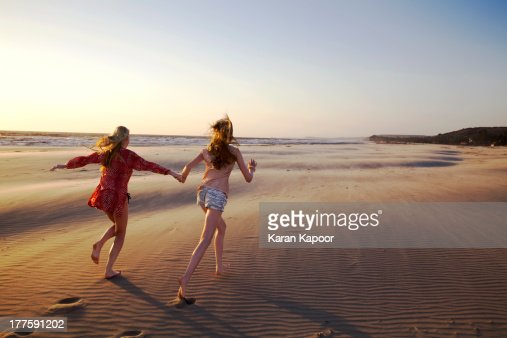 Maother and daughter running on empty beach : Stock Photo