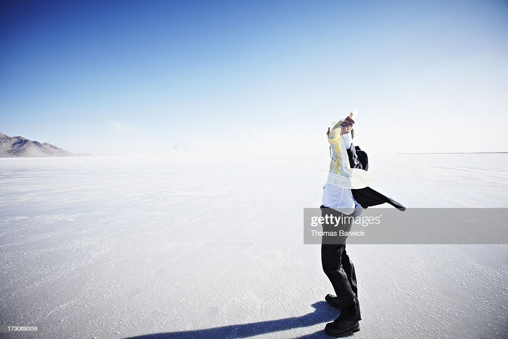 Map covering face of businessman on salt flats : Stock Photo