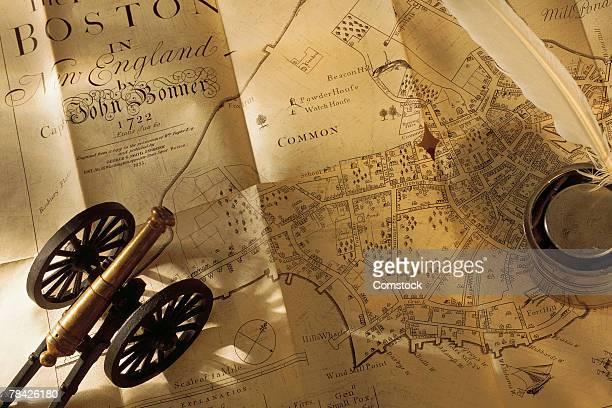 Map of Boston with miniature cannon and quill in inkwell