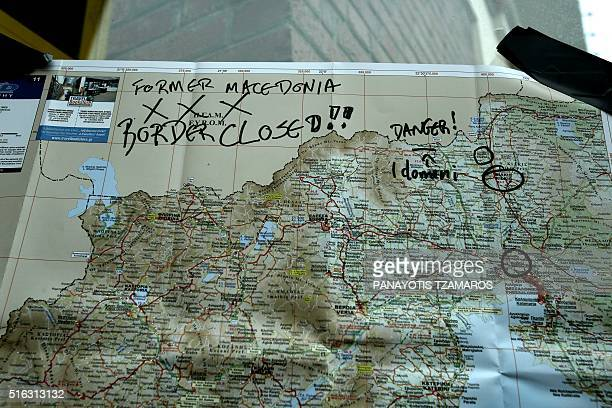 A map of Greece plastered at the passenger terminal at Piraeus port near Athens informs migrants and refugees about the border controls on March 18...