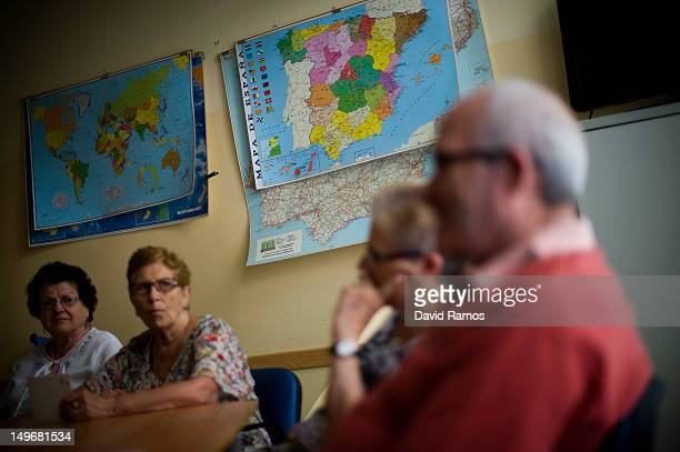 A map of Spain showing the autonomous regions hangs on a wall as elderly people listen a social worker during a memory activity at the Cuidem La...