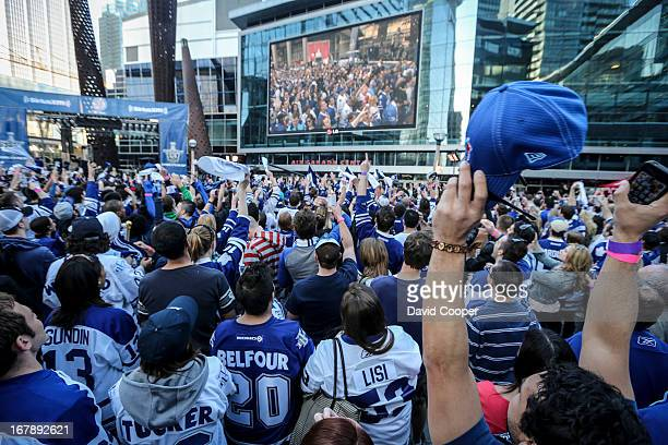 Maple Leaf fans cheer for themselves as they come up on the big screen in Maple Leaf Square during game one of the Leafs Bruins series outside the...
