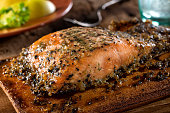A serving of delicious maple and smoked pepper cedar planked salmon.