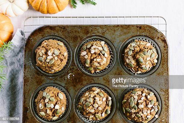 Maple Sweetened Pumpkin Oat Muffins are photographed from the top right after they came out of the oven in the muffin pan.