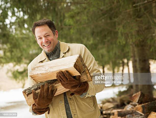 Maple Syrup Farm in the winter. A man carrying logs from the wood pile.