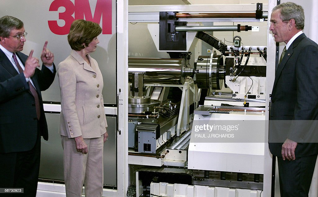 US President George W Bush and his wife Laura stand before a diamond turning machine during a tour of the 3M laboratory with 3M CEO George Buckley 02...