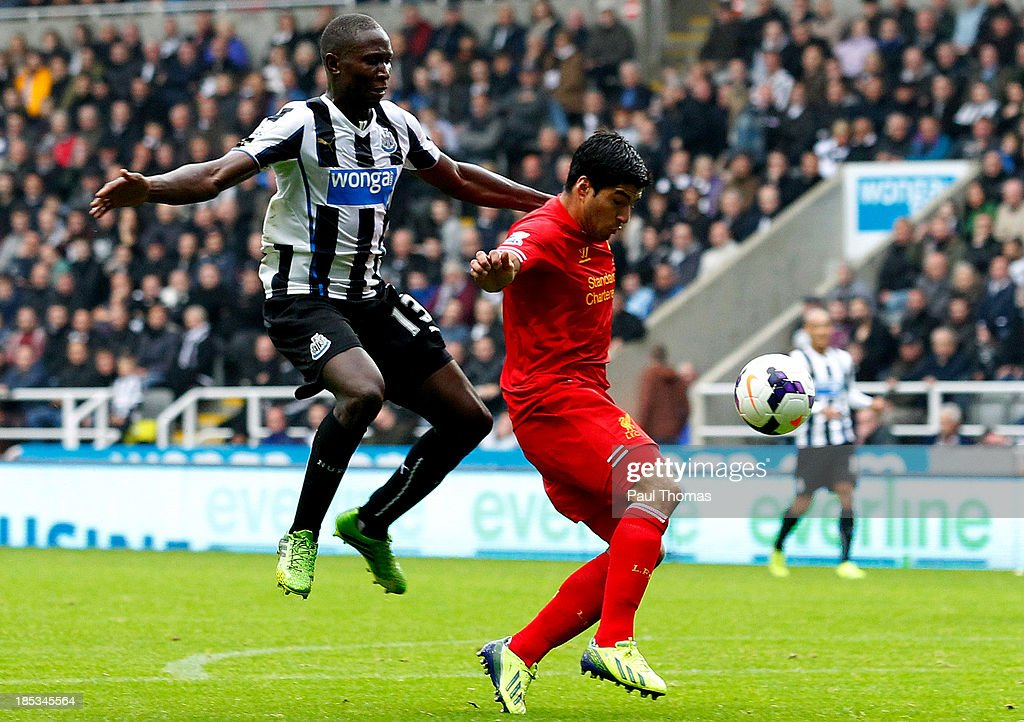 Mapou Yanga-Mbiwa (L) of Newcastle fouls Luis Suarez of Liverpool inside the penalty area before receiving a red card and conceding a penalty during the Barclays Premier League match between Newcastle United and Liverpool at St James' Park on October 19, 2013 in Newcastle-Upon-Tyne, England.