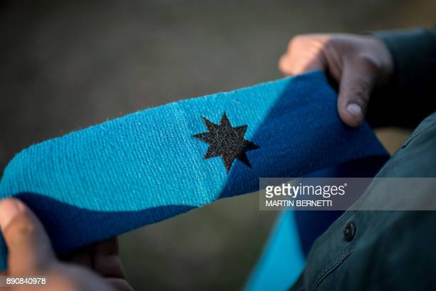 A Mapuche man holds a headband with El Gunelve Mapudungun a symbol of Mapuche iconography depicting an eightpointed star in Temuco on November 07...