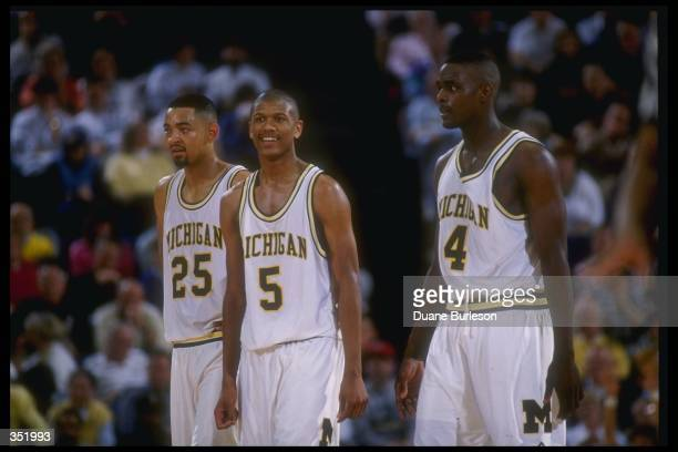 Michigan Wolverines forward Juwan Howard guard Jalen Rose and forward Chris Webber look on during a game against the Indiana Pacers