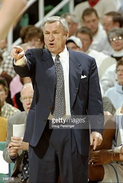 Coach Dean Smith of the North Carolina Tarheels gives instructions to his players during a playoff game against the Clemson Tigers at the Greensboro...