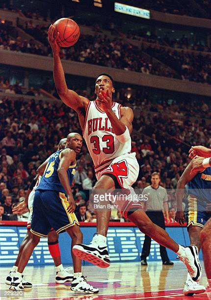 Forward Scottie Pippen of the Chicago Bulls goes up for the layup as guard Latrell Sprewell Golden State Warriors watches during their game at the...