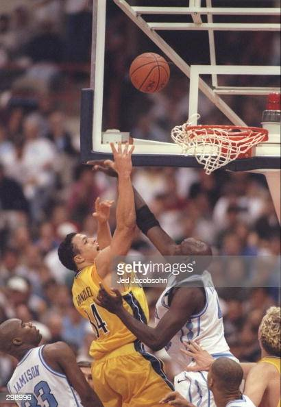 Center Makhtar Ndiaye of the North Carolina Tarheels and forward Tony Gonzalez of the California Bears fight for a rebound during a playoff game at...