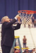 Coach Dean Smith of the North Carolina Tarheels cuts the net after a playoff game against the Louisville Cardinals at the Carrier Dome in Syracuse...