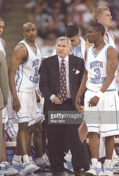 Coach Dean Smith speaks with guards Vince Carter and Shammond Williams of the North Carolina Tarheels during a NCAA Final Four game against the...