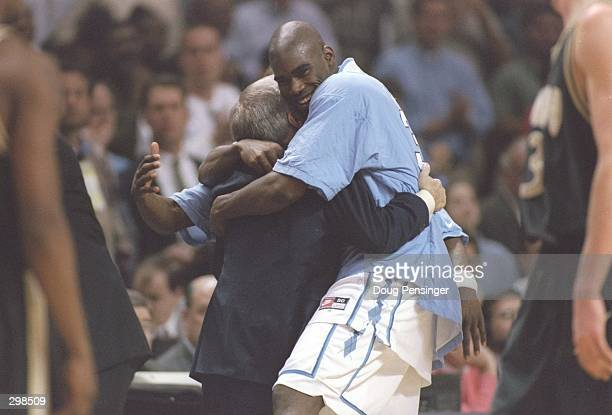 Foward Antawn Jamison of the North Carolina Tarheels hugs his coach Dean Smith after a playoff game against the Colorado Buffaloes at the Lawrence...