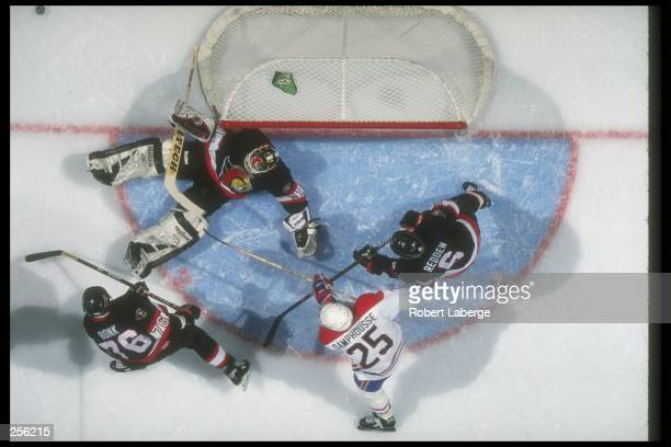 Goaltender Ron Tugnutt of the Ottawa Senators tries to make a save as teammates center Radek Bonk and defensemen Wade Redden tries to stop left wing...