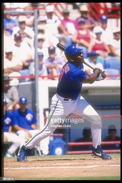 Joe Carter of the Toronto Blue Jays makes contact with a pitch during the Blue Jays versus Cincinnati Reds spring training game at Dunedin Stadium in...