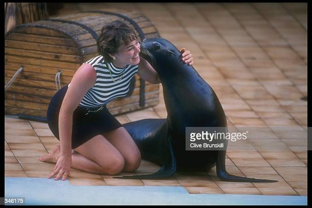 Martina Hingis of Switzerland smiles as she hugs a sealion during a visit to Sea World while competing in the Lipton Tennis Championships in Key...