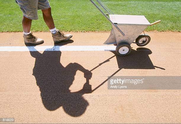 A member of the field crew chalks a line during a spring training game between the Atlanta Braves and the Cleveland Indians at Disney''s Wide World...