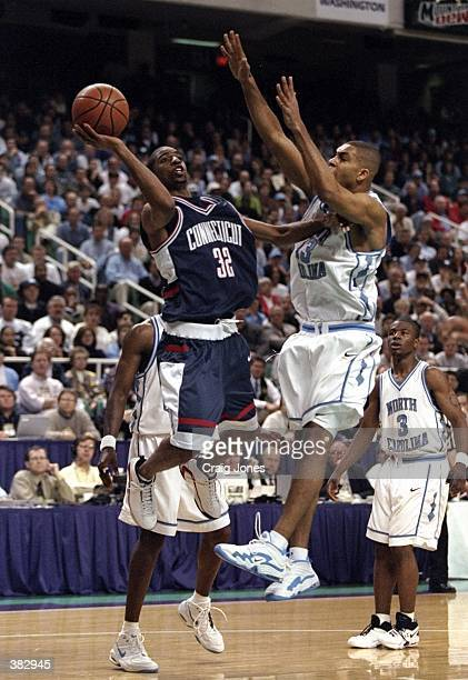 Guard Richard Hamilton of the Connecticut Huskies in action against forward Ademola Okulaja of the North Carolina Tar Heels during an NCAA East...
