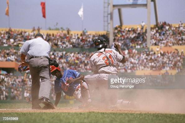 Catcher Charles Johnson of the Baltimore Orioles taggs Jose Estrada out during the game against the Cuban National Team at the Estadio...