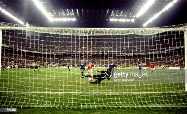 Paul Scholes of Manchester United slots the ball past a diving Gianluca Pagliuca of Inter Milan to score the equaliser in the UEFA Champions League...