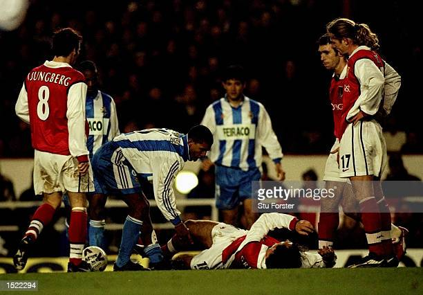 Djalminha of Deportivo La Coruna apologises to Gilles Grimandi of Arsenal during the UEFA Cup fourth round first leg game played at Highbury in...