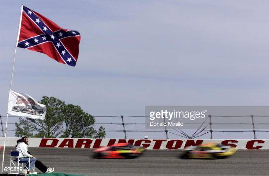 Beneath the old Confederate States flag the the 'stars and bars'' a fan watches the racers flash past the wall during the NASCAR Winston Cup Carolina...