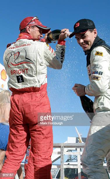 Jason Bright of the Holden Racing Team celebrates with second place getter Craig Lowndes of the Gibson Motorsport Team after race two of Round One of...