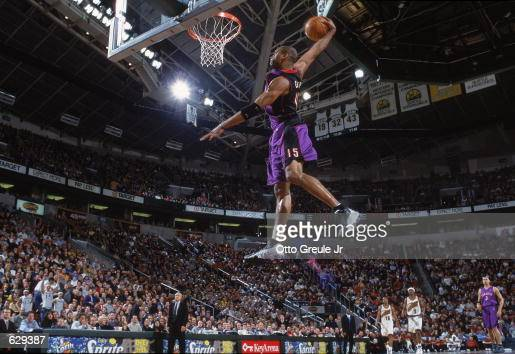 Vince Carter of the Toronto Raptors makes a slam dunk during the game against the Seattle SuperSonics at the Key Arena in Seattle Washington The...