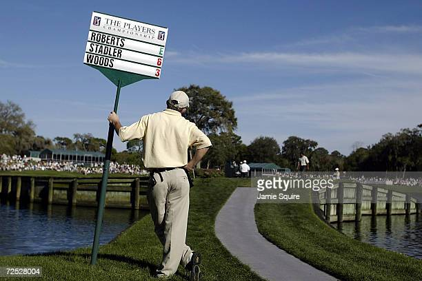 A sign bearer waits while players play the 17th green during Saturday's's third round of the Players Championships at the TPC at Sawgrass in Ponte...