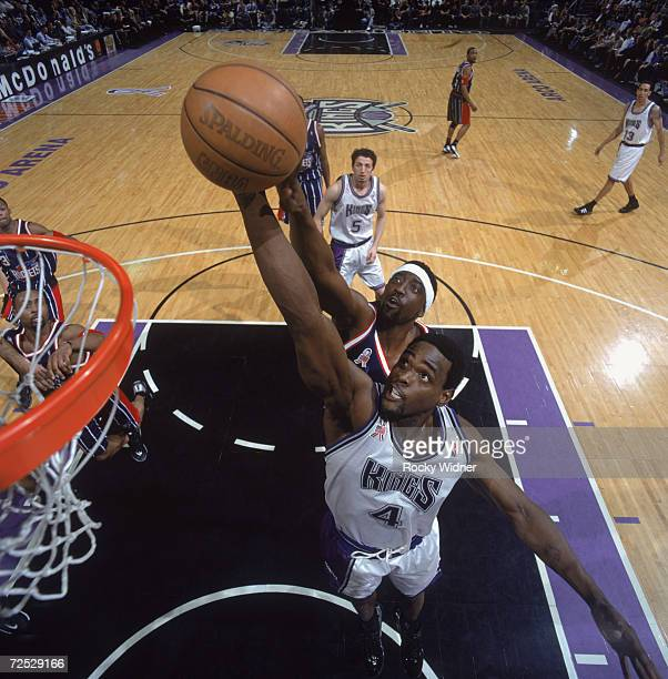 Chris Webber of the Sacramento Kings leaps to make a basket as he is guarded by Walt Williams of the Houston Rockets at the ARCO Arena in Sacramento...