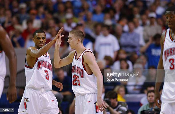 Juan Dixon and Steve Blake of Maryland hifive each other during the semifinal round of the NCAA Men's Final Four against Kansas at the Georgia Dome...