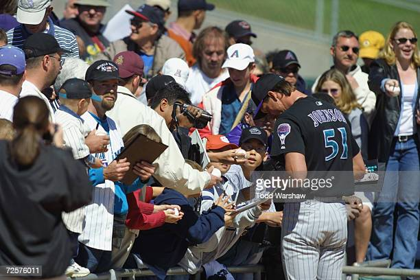 Randy Johnson of the Arizona Diamondbacks signs autographs during the Spring Training Game against the Chicago White Sox at Tucson Electric Field in...