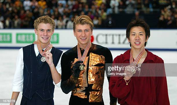 Silver medallist Timothy Goebel of USA gold medallist Alexei Yagudin of Russia and bronze medallist Takeshi Honda of Japan pose on the podium after...