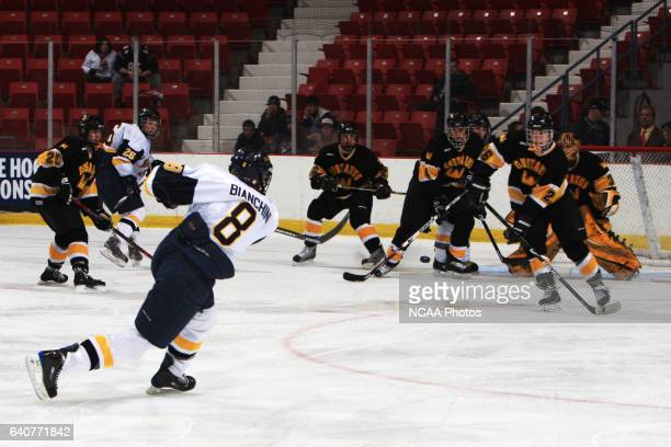 Neumann's Sean Bianchini takes a shot through a crowd of Gustavus Adolphus players during the Division III Men's Ice Hockey Championship game at the...