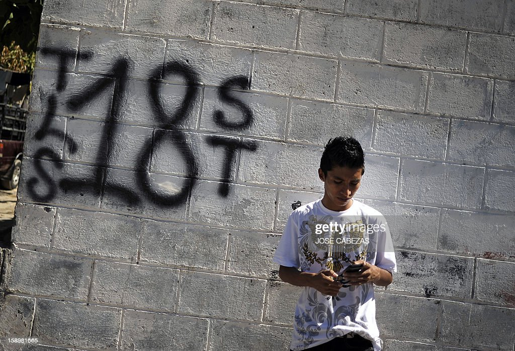 A 'Mara 18' street gang member stands by a graffiti before it is erased at Valle del Sol neighborhood in Apopa, 14 km north of San Salvador, El Salvador on January 4, 2013. Raul Mijango, Gang truce mediator, announced that 18 districs in El Salvador will be considered 'Sanctuary Territories' for gangs as a second stage of the gang truce. AFP PHOTO/ Jose CABEZAS