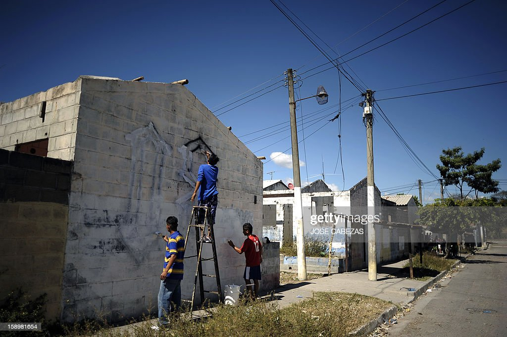 'Mara 18' street gang members erase a graffiti at Valle del Sol neighborhood in Apopa, 14 km north of San Salvador, El Salvador on January 4, 2013. Raul Mijango, Gang truce mediator, announced that 18 districs in El Salvador will be considered 'Sanctuary Territories' for gangs as a second stage of the gang truce. AFP PHOTO/ Jose CABEZAS
