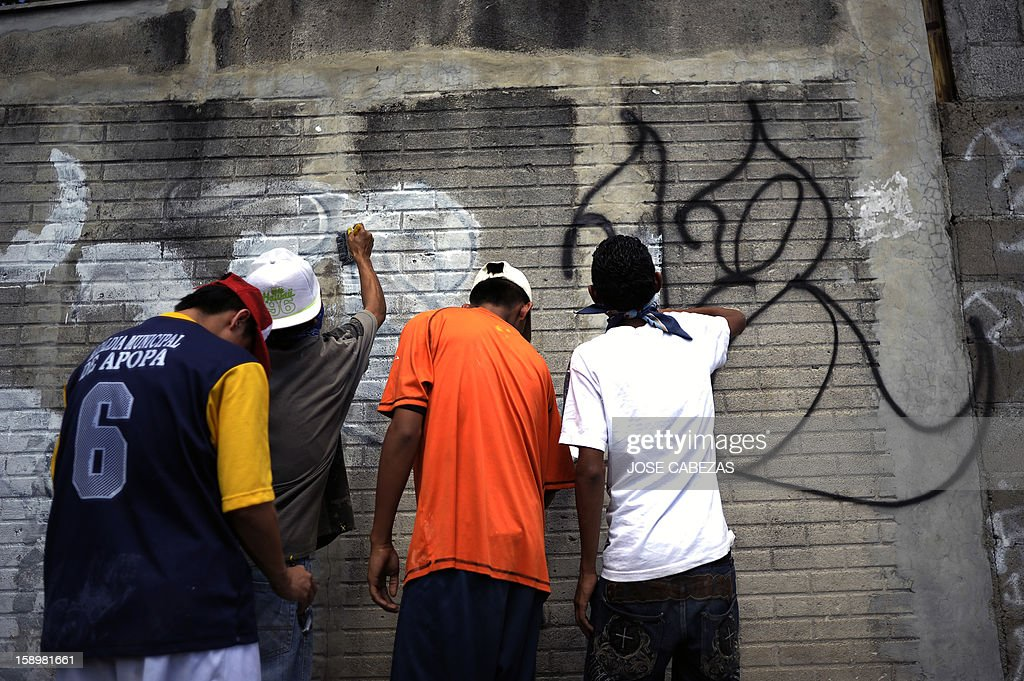 'Mara 18' street gang members erase graffitis at Valle Verde neighborhood in Apopa, 14 km north of San Salvador, El Salvador on January 4, 2013. Graffitis started to be erased as Raul Mijango, Gang truce mediator, announced that 18 districs in El Salvador will be considered 'Sanctuary Territories' for gangs as a second stage of the gang truce. AFP PHOTO/ Jose CABEZAS