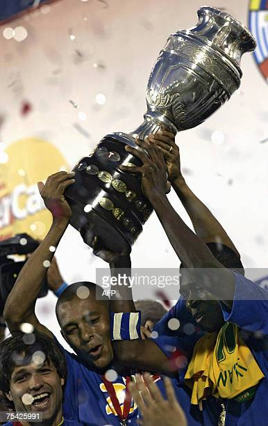 Brazilian captain Juan and Gilberto Silva hold up the trophy next to Diego during the award ceremony after winning the Copa America 2007 final match...