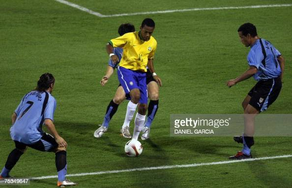 Brazilian forward Robinho vies for the ball with Uruguayan defender Andres Scotti while teammates midfielder Cristian Rodriguez and defender Dario...